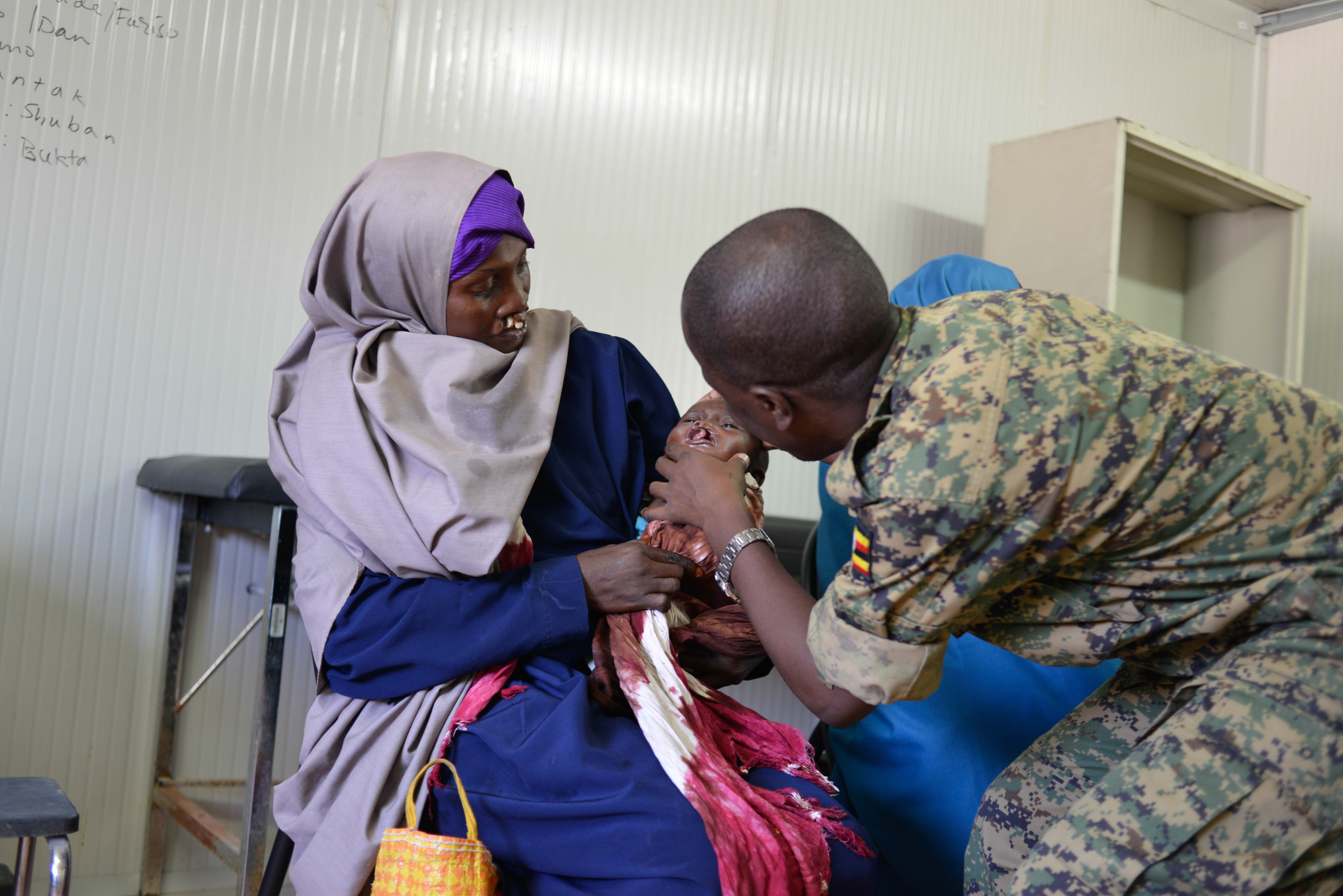An AMISOM paramedic checks a baby before his surgery in Mogadishu, Somalia, on October 31, 2016. Children born with a cleft lip have a  congenital defect that prevents them talking, eating and breathing properly. Medical teams from AMISOM, and partners from the international cleft lip charity Smile Train and Bancroft Global Development, conducted the cleft lip and cleft palate surgery. AMISOM Photo / Omar Abdisalan